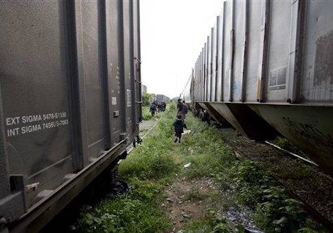 In this Saturday, July 12, 2014, photo, a migrants walk bewtween trains after getting off one during their journey toward the U.S.-Mexico border, in Ixtepec, southern Mexico. The migrants pay thousands of dollars per person for the illegal journey across thousands of miles in the care of smuggling networks that in turn pay off government officials, gangs operating on trains and drug cartels controlling the routes north. (AP Photo/Eduardo Verdugo)
