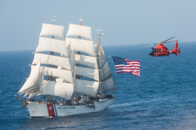 "An MH-65 ""Dolphin"" helicopter flies with the U.S. Coast Guard barque Eagle in the Atlantic Ocean on Thursday, July 30, 2015. The barque Eagle is the only active commissioned sailing vessel in American military service. (U.S. Coast Guard photo by Auxiliarist David Lau)"